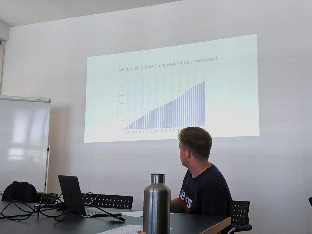 Moritz Faller (Referent) erklärt anhand einer Grafik, wie sich die Nutzerzahlen auf Facebook entwickelt haben.
